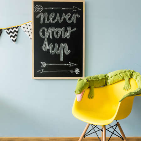 Shot of a blackboard and a chair with green crocodile toy Stockfoto