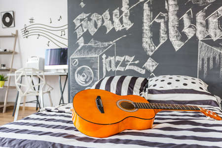 Shot of a guitar laying on a bed in a black and white music inspired modern bedroom