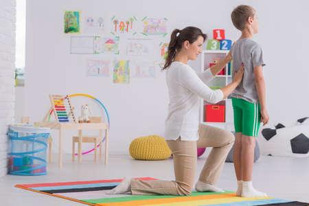 Fisioterapeuta joven corrigiendo la postura corporal de un niño de escuela