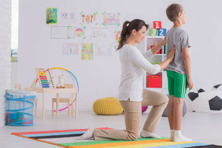 Jeune physiothérapeute corrigeant la posture corporelle d'un écolier