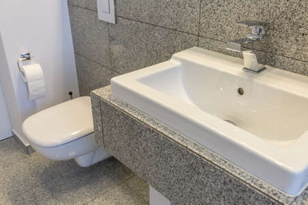 Modern toilet with grey tiles and white walls