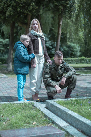 Soldier with his wife and son visiting grave