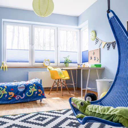 Modern schoolboy's room arranged in blue and white, with lots of practical accessories