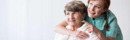 Jonge mooie verzorger en oudere gelukkige vrouw Stockfoto