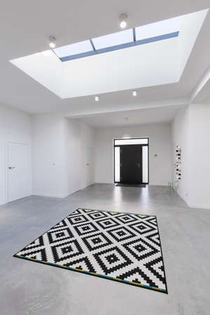 Spacious, bright, white hall with black front door and window in the ceiling Stock fotó