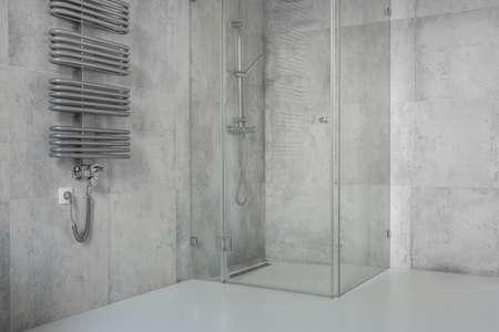 Ruime, moderne, minimalistische badkamer met betonnen tegels en glazen douchecabine
