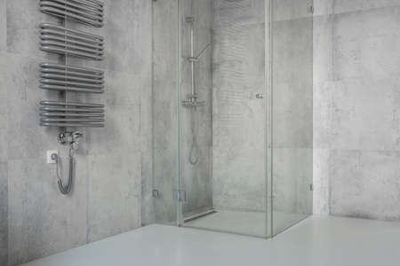 Spacious, modern, minimalist bathroom with concrete tiles and glass shower cabin