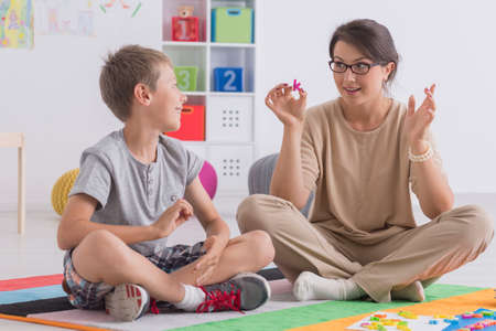 color therapist: Professional babysitter playing educational game with a school-boy Stock Photo
