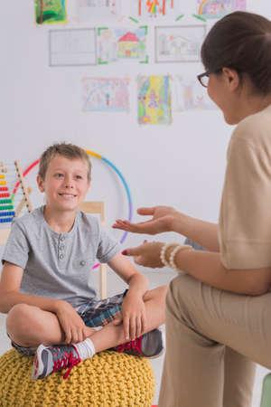 psicologia infantil: Psicoterapeuta hablar con un niño pequeño, sentado en una luz interior Foto de archivo
