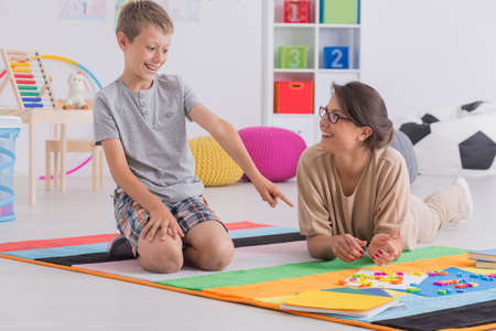 color therapist: Smiling professional babysitter and happy school-boy playing together