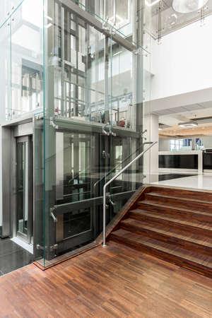 Couloir moderne avec parquet en bois élégant, escaliers et ascenseur vitré moderne Banque d'images