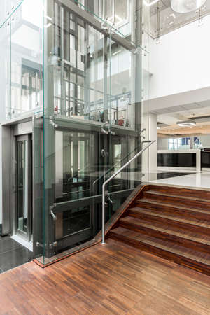Modern corridor with elegant wooden parquet, stairs and modern glazen elevator