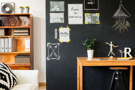 Drawing table with artists accessories by blackboard wall with motivational posters in stylish modern flat