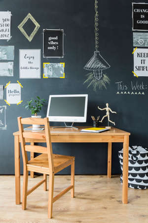 Wooden computer desk and chair by a chalkboard wall with optimistic phrases