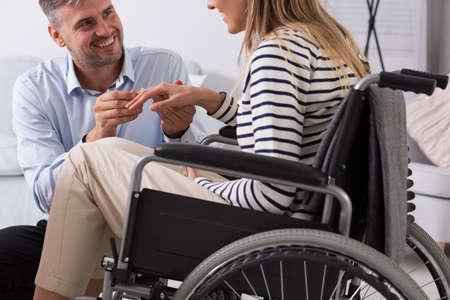 respetar: Alegre hombre pone anillo en el dedo de una mujer en una silla de ruedas