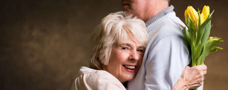 fondness: Older smiling woman snuggles up to her partner and holds a bouquet of tulips