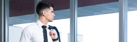 without window: Young businessman without jacket looking through the window Stock Photo