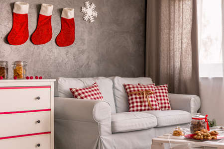 frohe: Lounge with white sofa and stockings above it waiting for christmas time Stock Photo