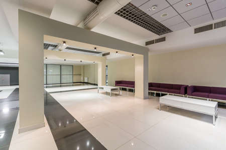 elective: Wide modern corridor with white pillars, white and grey tiles on the floor and purple seats by wall
