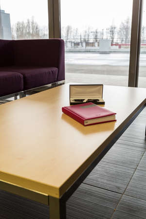elective: Modern desk with the pen and the book of masters thesis on, with the couch and large window at the background Stock Photo