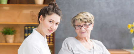 keeping room: Young nurse sitting close to the senior woman in her home with the table and chest of drawers at the background Stock Photo