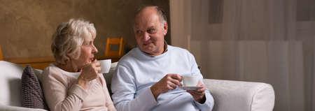 tomando café: Pareja de ancianos sentados en un sofá y bebiendo una taza de café Foto de archivo