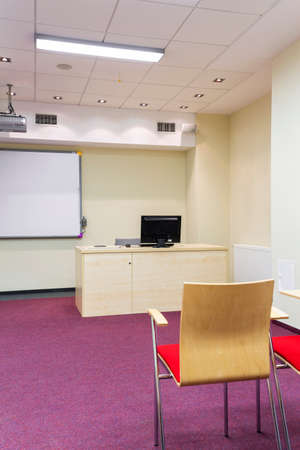 elective: Bright simple classroom with a desk, chairs, board and purple carpet