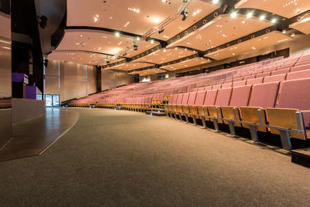 elective: Large space of lecture hall in academy with modern backlight on dropped ceiling, wooden seats and the platform lectern