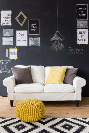 Sophisticated blackdesign interior with white comfortable sofa standing by a blackboard wall full of motivational phrases