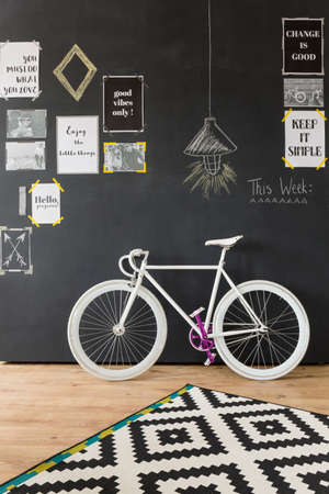 Modern interior design with bicycle with white wheels and frame standing by a chalkboard wall with slogans on it