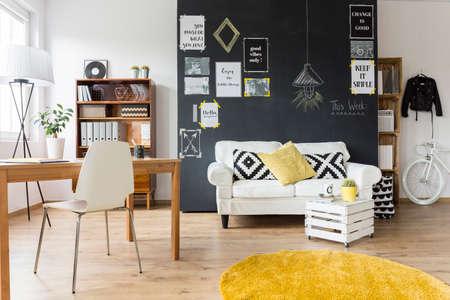 sala de estar creativa con la pared de pizarra, escritorio de madera y muebles de época Foto de archivo