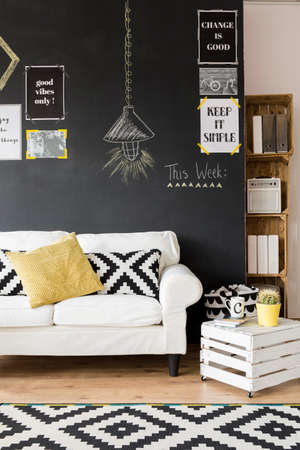 citations: Fragment of optimistic living room with white sofa and motivational phrases on the wall Stock Photo