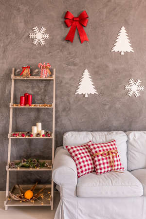 frohe: Shelf with christmas decorations near white sofa in lounge