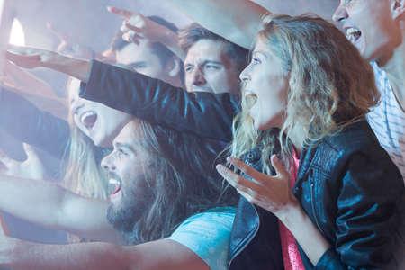Jong meisje staande in een menigte van mensen, plezier op een rock concert