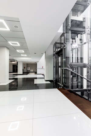 Modern black and white corridor with white ceiling with backlight, snowy-white tiles on the floor and glazed lift shaft Stock Photo