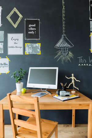 Modern room with desk space by chalkboard wall, with computer, tablet and wooden figurine
