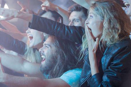 ロック コンサートで興奮した人々 の群衆の中に立っている若い女性 写真素材