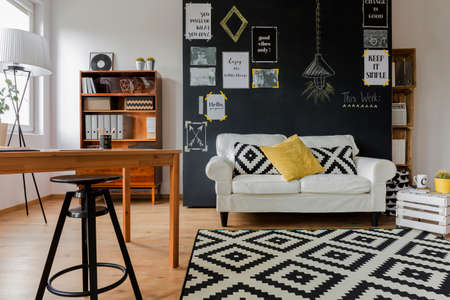 citations: Pleasant interior of a contemporary flat, with a drawing table and high black stool