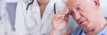 saddened: Saddened older man is sitting worry and female doctor trying to comfort him