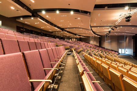 elective: Large space of lecture hall in academy, with modern backlight and many wooden seats Stock Photo