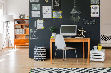 citations: Creative working space with computer desk and accessories in flat with blackboard wall