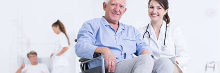 Elderly man on a wheelchair and young female doctor are smiling