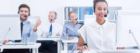 servicio al cliente: área de la oficina de trabajo brillante con empleados satisfechos Foto de archivo