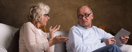 Upset elderly woman explaining something to her husband