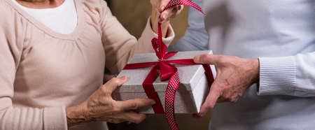 fondness: Man is holding a box with a gift while a woman is pulling a decorative ribbon