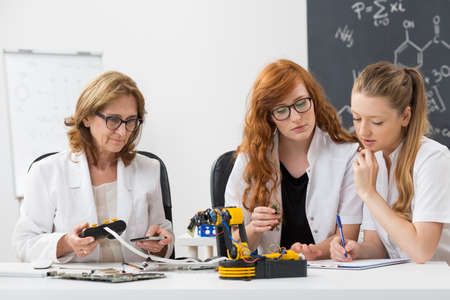 technical university: Shot of technical university teacher working on a new project with her students Stock Photo