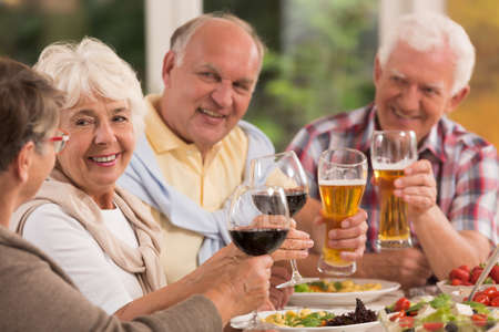 Happy elderly friends drinking beer and wine during dinner