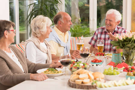 Group of happy seniors eating a dinner, drinking beer and wine