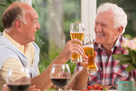 an old friend: Two happy senior friends drinking a beer during dinner Stock Photo