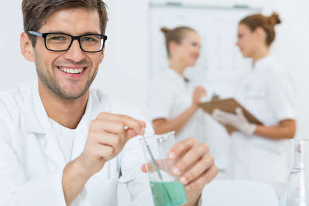 Young scientist conducting an experiment, two women wearing labcoats in the background